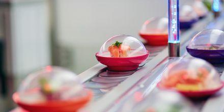 Sushi på rullebånd. Et vanlig skue på restauranter i Japan.