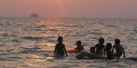Barn som koser seg på stranden