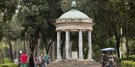 I Parken Villa Borghese venter fine statuer, vegetasjon og monumenter.