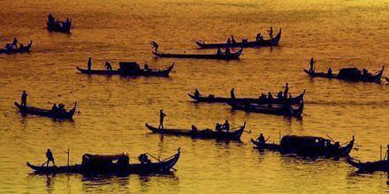 Long-tail båter i solnedgang.